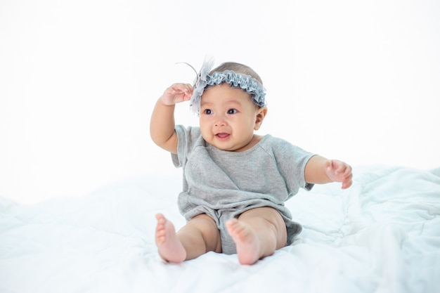 Happy baby sitting on a white bed