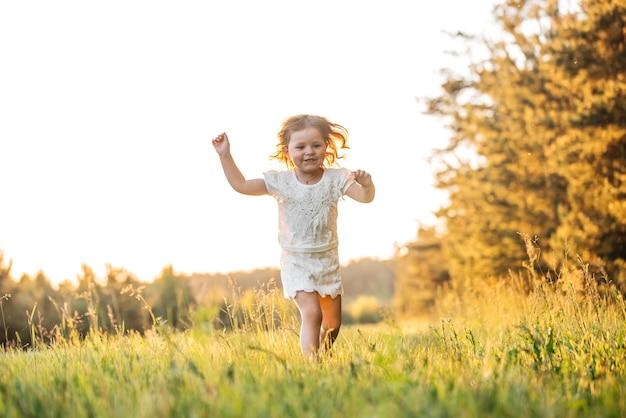 幸せな赤ちゃんの笑顔。屋外の日没で走っている少女。
