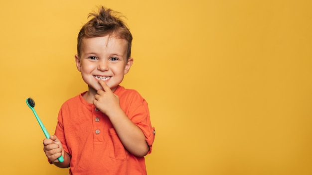 Happy baby toddler boy brushing his teeth with a toothbrush on a yellow background. health care, oral hygiene. a place for your text.