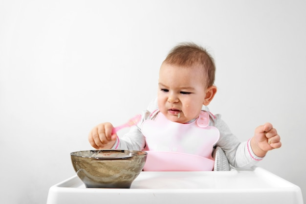 Happy baby toddler in high chair with spoon in his hand