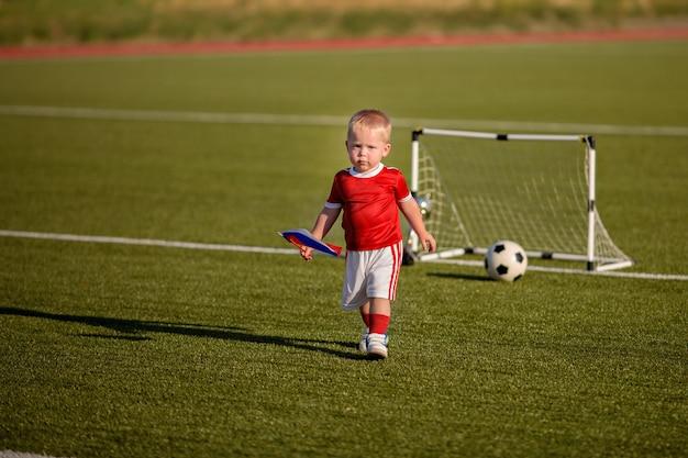 ゲート近くのフィールドでボールとサッカーをして幸せな赤ちゃん男の子