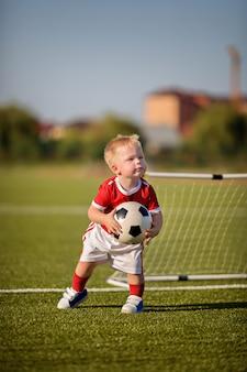 Счастливый маленький мальчик играет в футбол с мячом на поле возле ворот