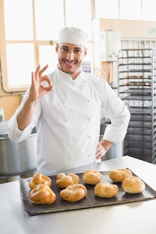 Happy baker showing tray of rolls in the kitchen of the bakery
