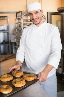 Счастливый пекарь, вынимающий свежие бублики