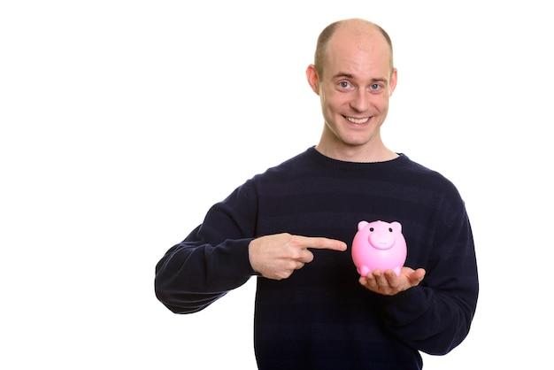 웃 고 돼지 저금통을 들고 행복 한 대머리 백인 남자