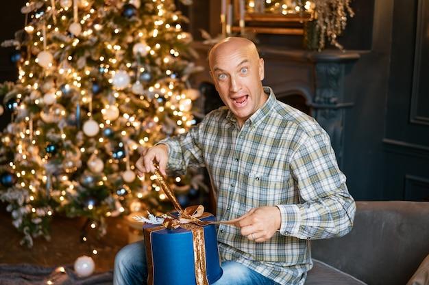 셔츠를 입은 행복한 대머리 남자는 배경에 대해 소파에 앉아 있는 동안 크리스마스 선물을 엽니다...