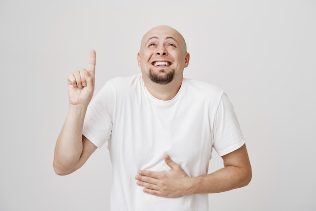 Happy bald middle-aged man laughing over copyspace, pointing up as chuckle