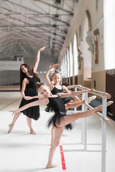 Happy ballerina girls practicing ballet on barre with their coach