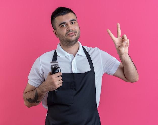Felice barbiere in grembiule che tiene il trimmer guardando la telecamera sorridendo allegramente mostrando il segno a v in piedi su sfondo rosa
