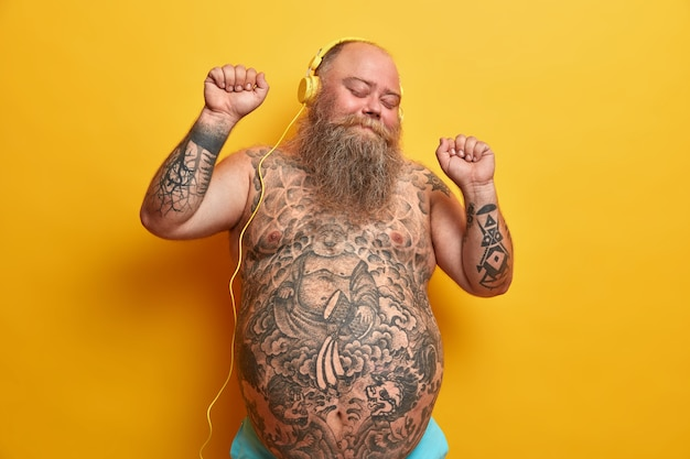 Happy bare man with fat stomach, tattooed belly, enjoys listening new song in headphones, raises arms, clenches fists, moves with rthythm, feels carefree, enjoys fantastic bits, poses indoor