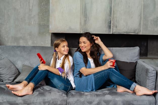 娘と一緒に幸せな裸足の母はソファの上に座る