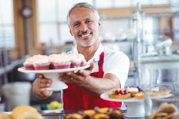 Happy barista smiling at camera and holding a plate of cupcakes