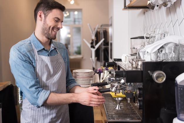 Счастливый бариста. молодой красивый мужчина смеется и использует кофеварку, стоя за стойкой.