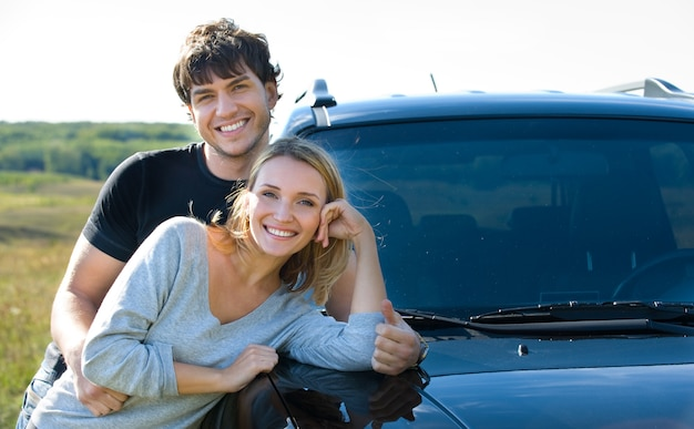 車の近くに立っている幸せな生意気な若いカップル