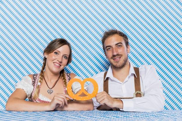 Happy bavarian couple holding a pretzel