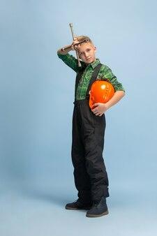Felice di esserlo. ragazzo che sogna la professione di ingegnere. infanzia, pianificazione, educazione, concetto di sogno. vuole essere un impiegato di successo nel settore manifatturiero, edile, delle infrastrutture, delle riparazioni.