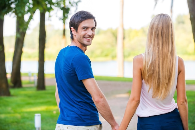 Happy to be with her. rear view of handsome young man looking over shoulder and smiling while walking along the park road with his girlfriend