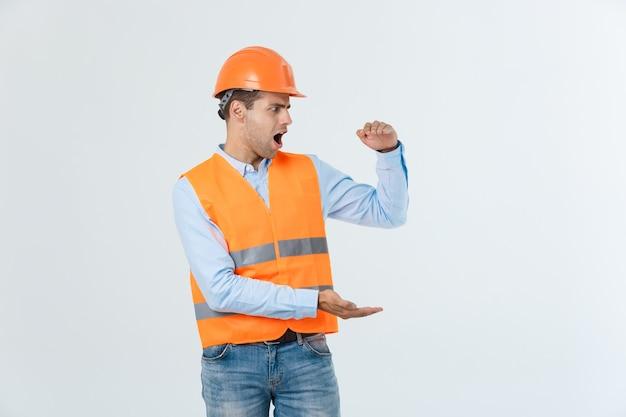 横に手を握って何かを説明する幸せなひげエンジニア、白い背景で隔離の黄色いベストとオレンジ色のヘルメットとカロシャツとジーンズを着ている男。