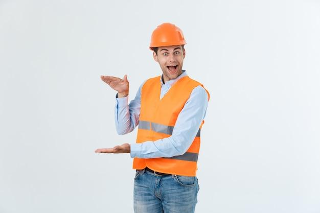 흰색 배경에 격리된 노란색 조끼와 주황색 헬멧이 달린 카로 셔츠와 청바지를 입은 행복한 수염 엔지니어가 손을 잡고 뭔가를 설명하고 있습니다.