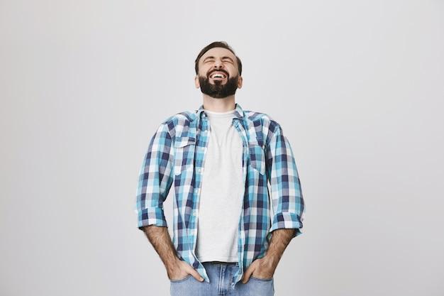 Счастливый бородатый взрослый мужчина смеется уд