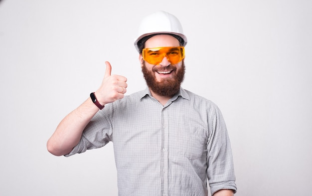 A happy bearded architect wearing a helmet and a pair of protection glasses is showing a thumb up to the camera near a white wall