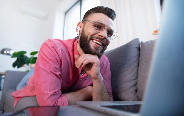 家やアパートのソファにラップトップを持って眼鏡とカジュアルな服装で幸せなひげを生やした魅力的な若い男はリラックスまたは働いています
