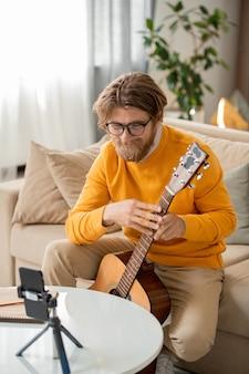 ソファに座ってオンラインの聴衆に音楽の作り方を教えながらスマートフォンのカメラを見てギターを持った幸せなひげを生やした金髪の男