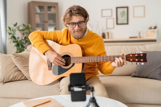 Счастливый бородатый блондин с гитарой смотрит в камеру смартфона, сидя на диване и учит онлайн-аудиторию сочинять музыку