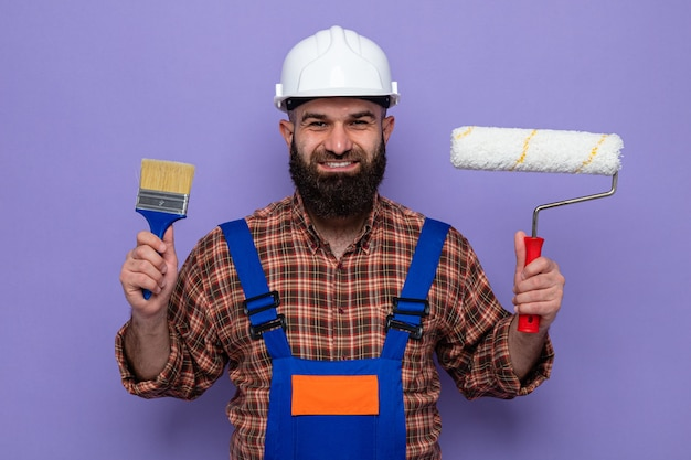 Felice costruttore barbuto in uniforme da costruzione e casco di sicurezza che tiene rullo di vernice e pennello che sorride allegramente