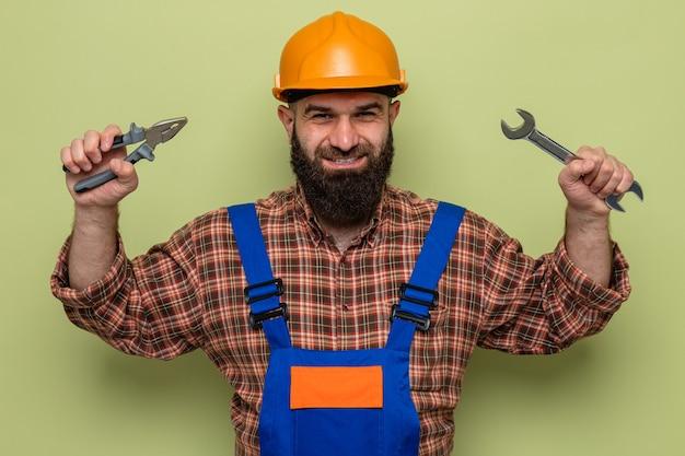 Felice costruttore barbuto in uniforme da costruzione e casco di sicurezza che tiene in mano una chiave inglese e una pinza che sembra sorridente allegramente