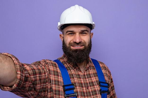 紫色の背景の上に広く立って自分撮り幸せで陽気な笑顔を取っている建設制服と安全ヘルメットの幸せなひげを生やしたビルダーの男