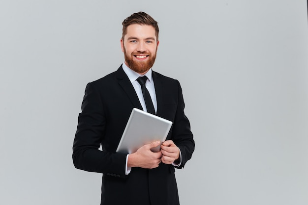 Happy bearded business man in black suit holding tablet computer