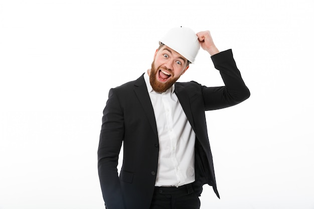 Happy bearded business man in protective helmet knocks on it