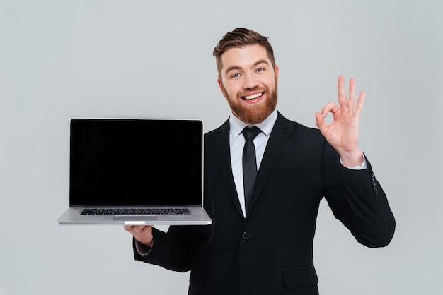 빈 노트북 화면을 표시하고 확인 표시를 보여주는 행복한 수염 사업가. 격리 된 회색 배경
