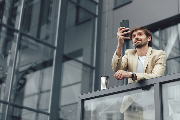 Happy bearded businessman in suit and wireless smartphone having video conference on smartphone outdoors