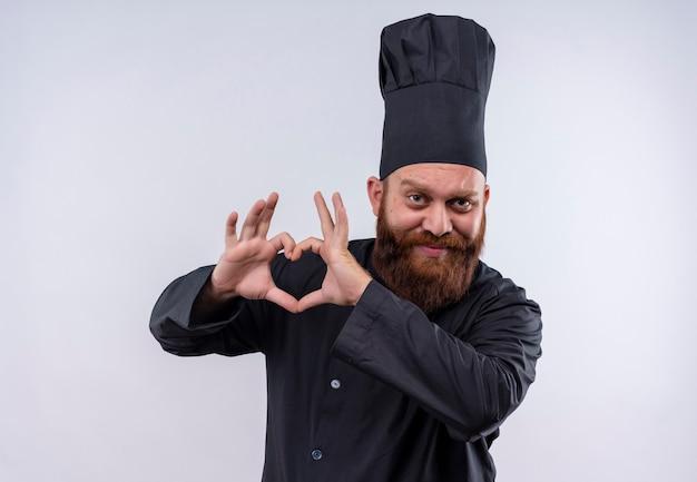 Un uomo felice chef barbuto in uniforme nera che mostra il segno di forma del cuore con le mani su un muro bianco
