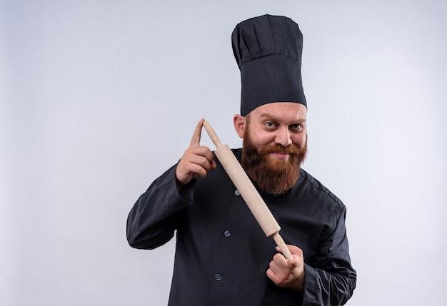 Un uomo felice chef barbuto in uniforme nera che mostra il mattarello mentre guarda la fotocamera su un muro bianco
