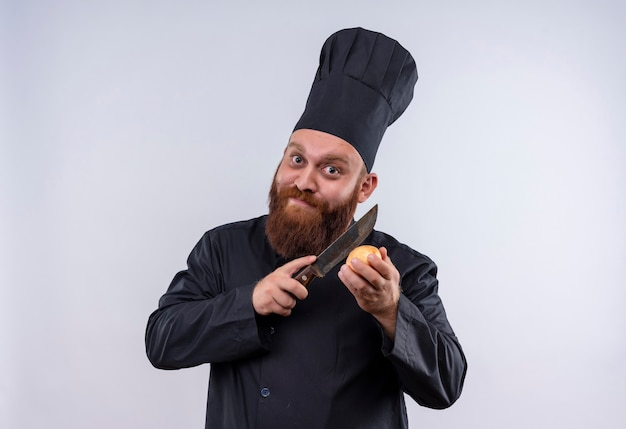 A happy bearded chef man in black uniform trying to cut onion with knife while looking at camera on a white wall