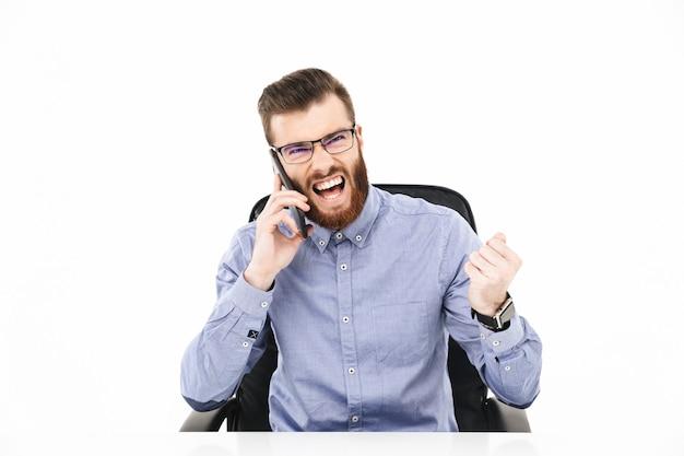 Счастливый бородатый элегантный мужчина в очках разговаривает по смартфону и радуется, сидя за столом