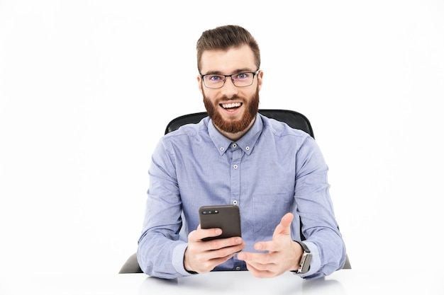 Счастливый бородатый элегантный мужчина в очках с помощью смартфона и глядя сидя за столом