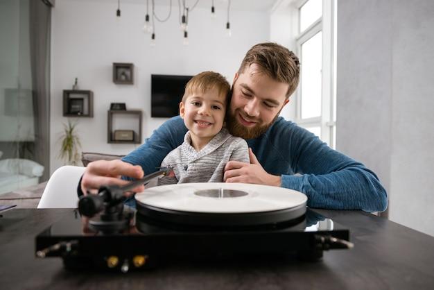 青いセーターを着た幸せなひげを生やした父親は、室内の部屋で彼の小さなかわいい息子と一緒にビニールレコードで音楽を聴いています