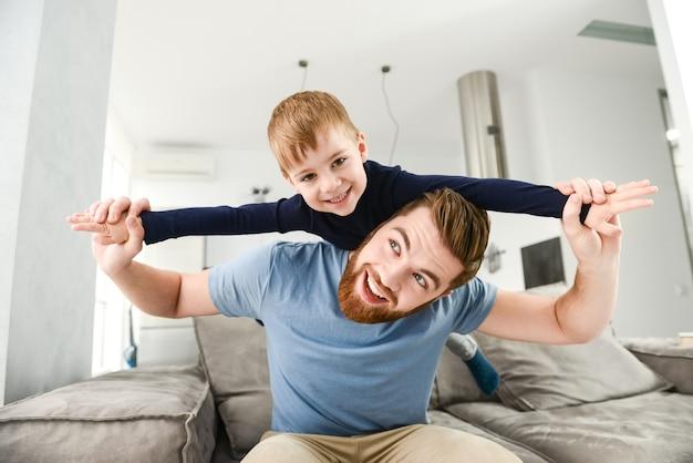 Счастливый бородатый отец, одетый в синюю футболку, играет со своим маленьким милым сыном в комнате