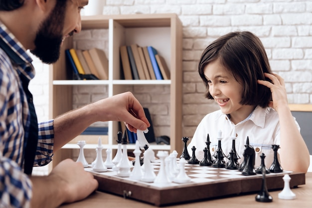Happy bearded father plays chess with teenage son.