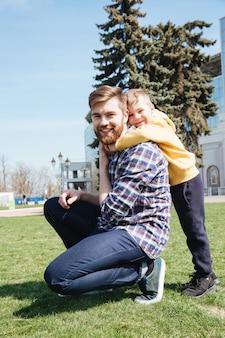 彼の幼い息子と歩いて幸せなひげを生やした父