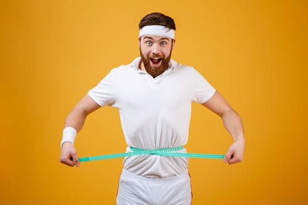 Happy bearded fitness man measuring his waist with tape