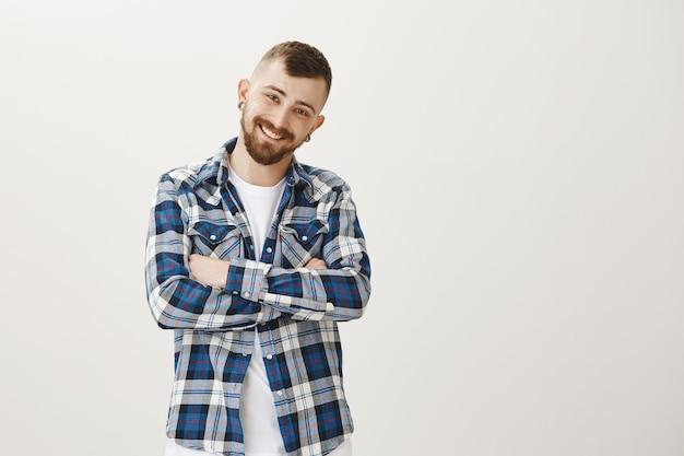 Счастливый бородатый парень в повседневной одежде закрывает глаза с энтузиазмом