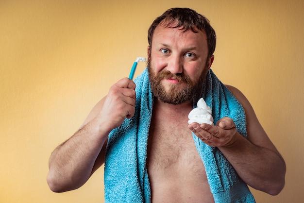 幸せなあごひげを生やした男は彼のあごひげを剃る準備ができています。髭剃りの男。
