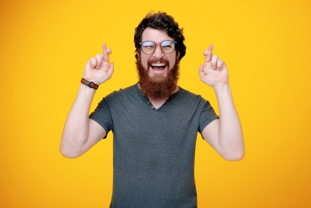 Happy bearded guy is while crossing finger for more luck, standing on yellow