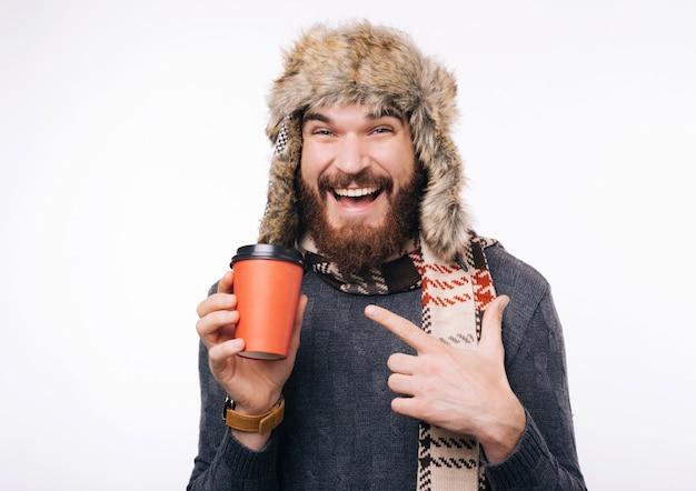 추운 날에 따뜻한 옷을 입고, 컵을 가리키며, 어떻게 몸을 따뜻하게하는지 보여주는 수염을 가진 행복한 수염 난 남자