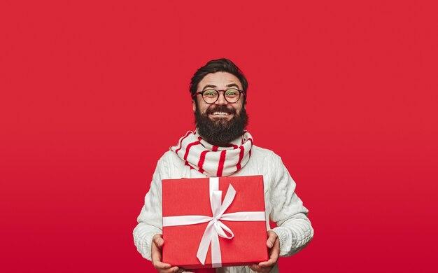 Счастливый бородатый хипстер с подарком на рождество
